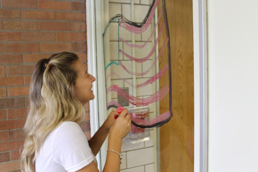 Junior Kaitlyn Houp helps paint the windows for the USA themed game in memoriam of 9/11.
